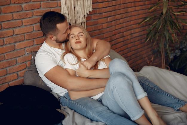 Paar sitzt auf einem bett in einem raum