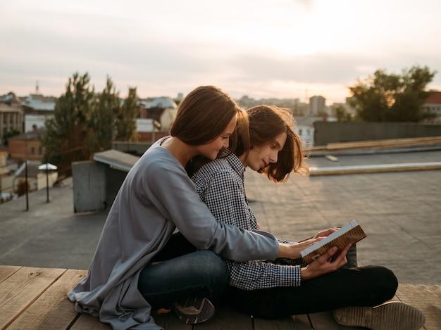 Paar sitzt auf einem dach und liest ein buch. literatur-selbstverbesserung, freizeit, hobby, bücherwürmer-konzept