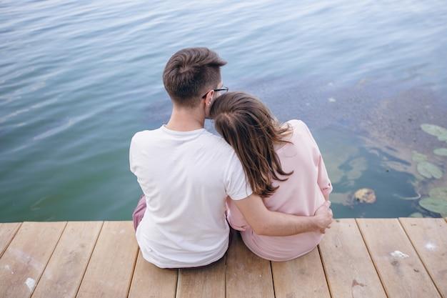 Paar sitzt auf einem holzsteg und den kopf auf die schulter von ihm ruhen