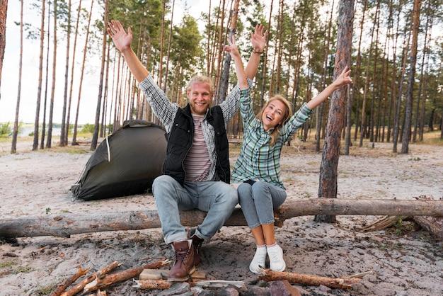 Paar sitzt auf einem umgestürzten baum mit den händen in der luft