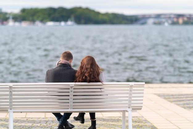 Paar sitzt auf einer bank mit blick auf unruhiges wasser an einem kalten, windigen herbsttag in ihren dicken mänteln in einer rückansicht