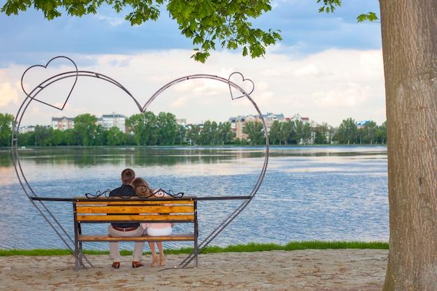 Paar sitzt auf einer bank vor einem großen see