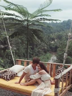 Paar sitzt auf einer großen schaukel auf einem bali
