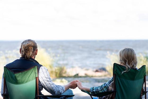 Paar sitzt auf stühlen und hält hände