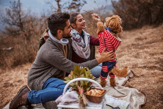 Paar sitzt beim picknick und spielt mit einem hund.