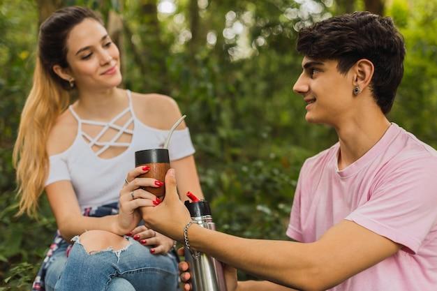 Paar sitzt im dschungel und trinkt mate-infusion
