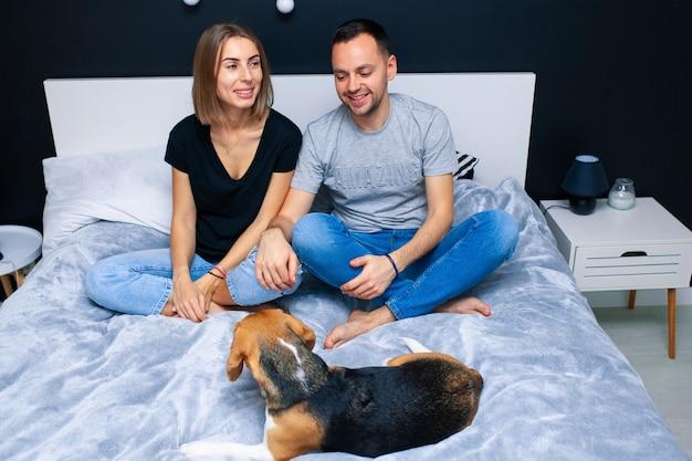 Paar sitzt im schlafzimmer mit ihrem hund