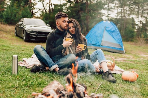 Paar sitzt in der nähe von lagerfeuer
