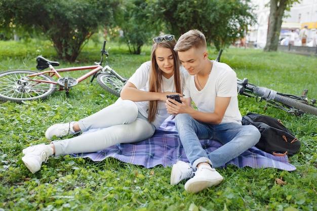 Paar sitzt in einem park mit fahrrad