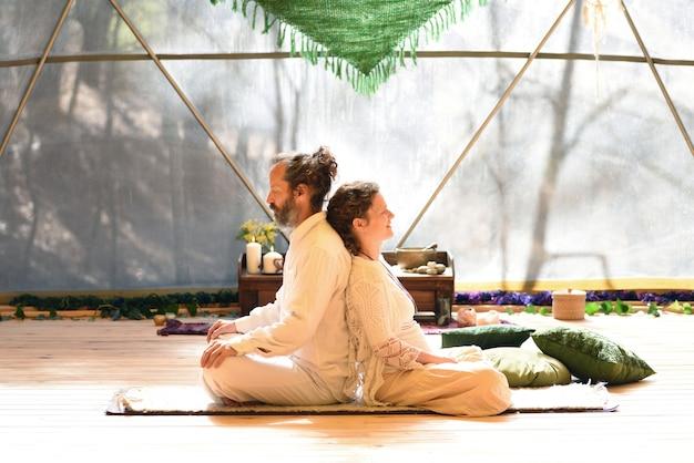Paar sitzt in lotussitzung und macht eine tantrische yoga-praxis