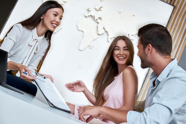 Paar sitzt mit manager im reisebüro und überprüft den vertrag