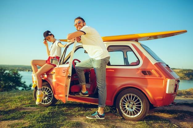 Paar sitzt und ruht am strand an einem sommertag in der nähe des flusses. kaukasischer mann und frau