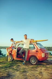 Paar sitzt und ruht am strand an einem sommertag in der nähe des flusses. liebe, glückliche familie, urlaub, reisen, sommerkonzept.