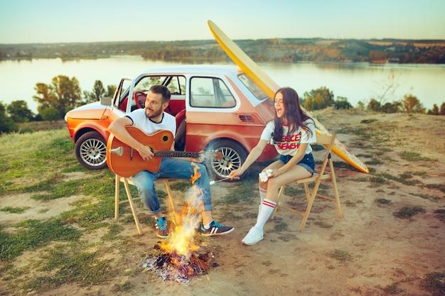 Paar sitzt und ruht sich am strand aus und spielt gitarre an einem sommertag in der nähe des flusses