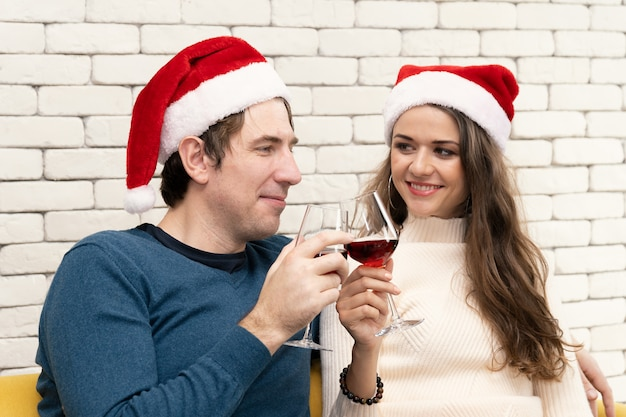Paar sitzt und trinkt rotwein auf dem sofa.