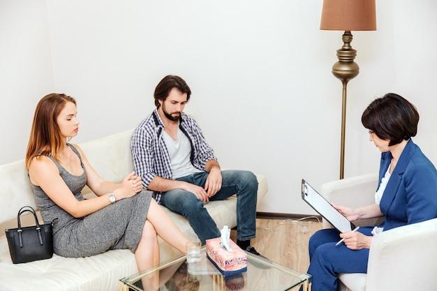 Paar sitzt vor arzt. sie schauen auf den boden. doktor sucht in ihren papieren. sie sitzen auf weißen sofas