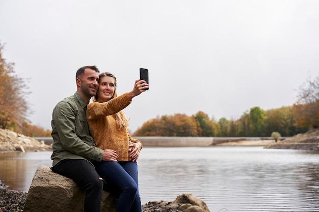 Paar sitzt vor dem see und macht ein selfie im freien mit einem see