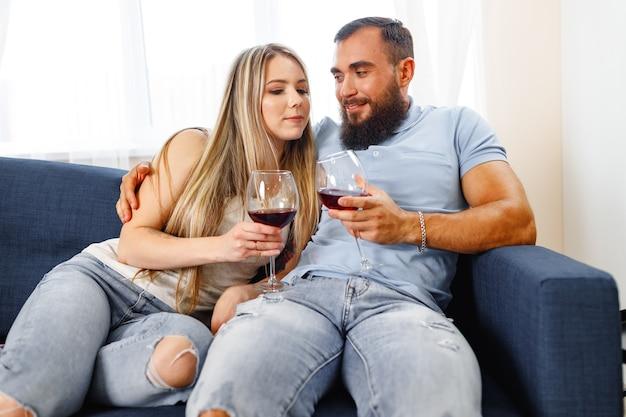 Paar sitzt zu hause auf dem sofa und trinkt wein