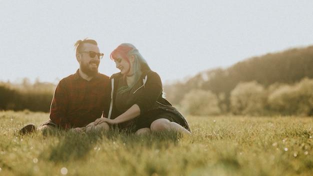 Paar sitzt zusammen auf dem feld