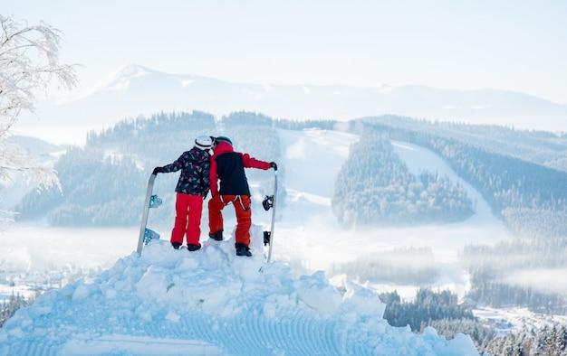 Paar snowboarder, die sich auf dem berg gegen schneebedeckte wälder und hügel im winterskigebiet küssen. rückansicht
