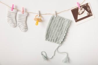 Paar Socken; Schnuller; Kopfbedeckung und Sonographie Bild hängen an der Schnur mit Wäscheklammer