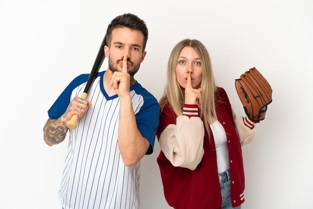 Paar spielt baseball über isoliertem weißem hintergrund und zeigt ein zeichen der stille geste, die finger in den mund steckt