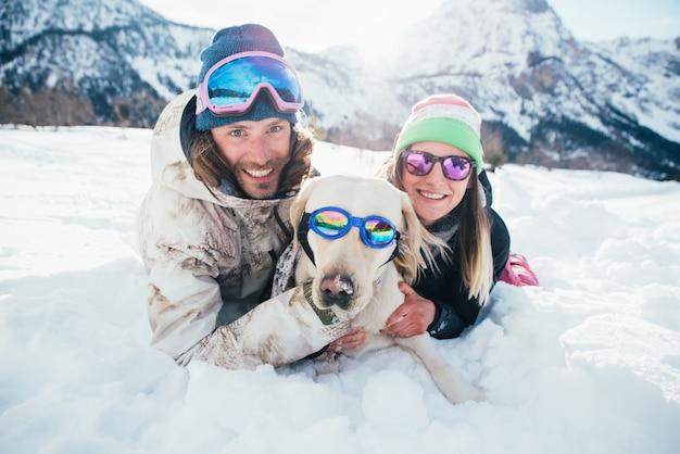 Paar spielt mit hund auf den bergen, auf dem schneebedeckten boden