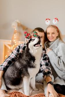 Paar spielt mit hund im schlafzimmer
