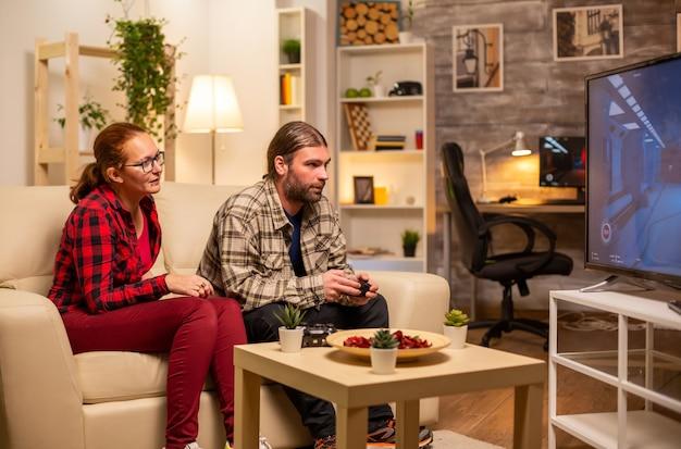 Paar spielt spät in der nacht videospiele auf einem großbildfernseher im wohnzimmer.