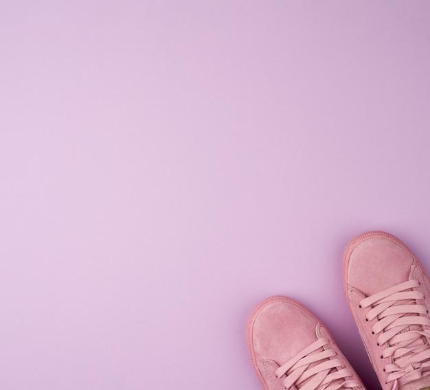 Paar sportliche rosa turnschuhe mit schnürsenkeln auf einem lila hintergrund