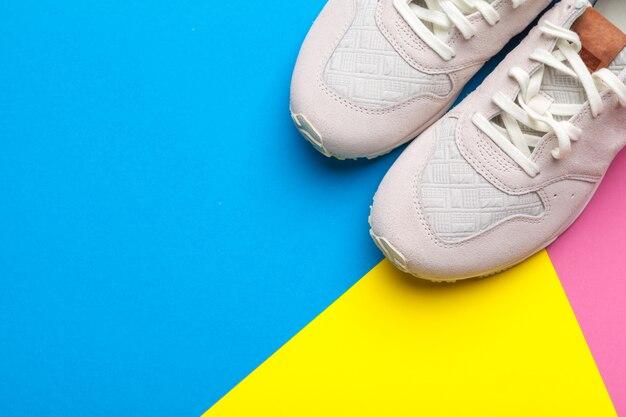 Paar sportschuhe auf blau, rosa und gelb