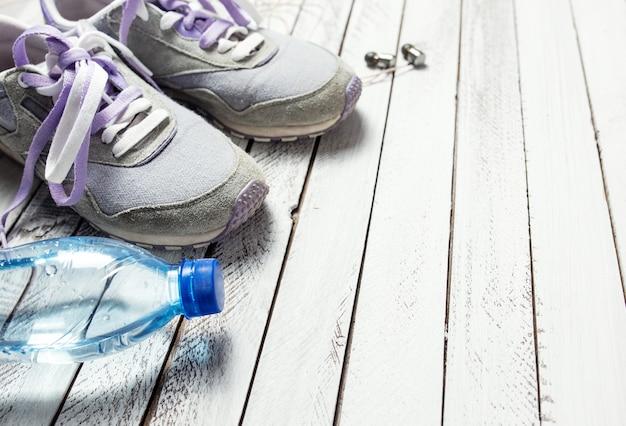 Paar sportschuhe, wasserflasche und kopfhörer auf weißem holzhintergrund