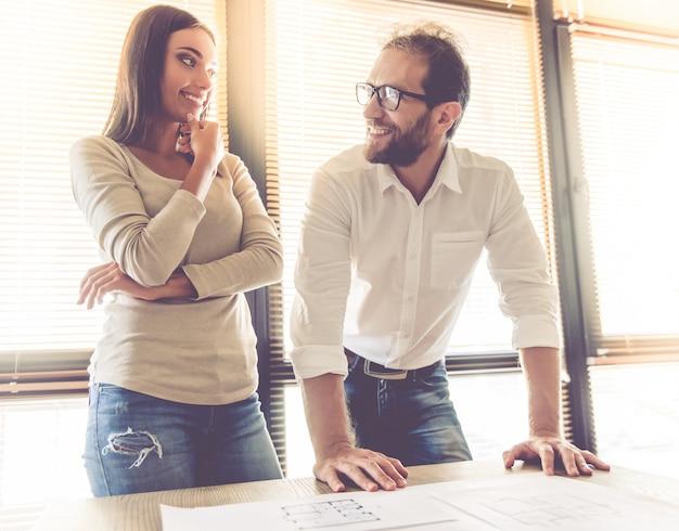 Paar spricht und lächelt beim arbeiten im büro