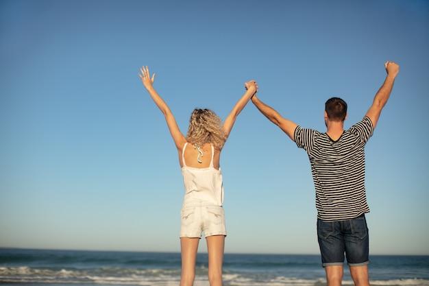 Paar stehend zusammen mit armen am strand