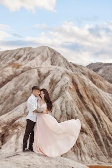 Paar steht am abgrund des berges und des roten sees und umarmt sich. die braut und der bräutigam verliebt, die frau in langem kleid in den armen der männer