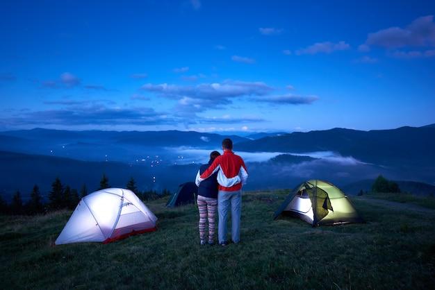 Paar steht in der nähe von camping mit dem rücken zur kamera umarmt sich