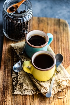 Paar tasse kaffee mit bohnen auf strukturiertem brett