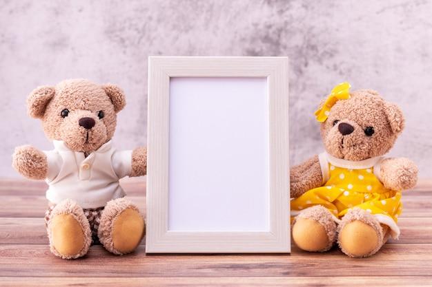 Paar teddybär mit bilderrahmen auf holztisch