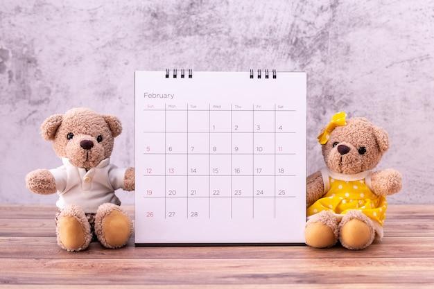 Paar teddybär mit kalender auf holztisch