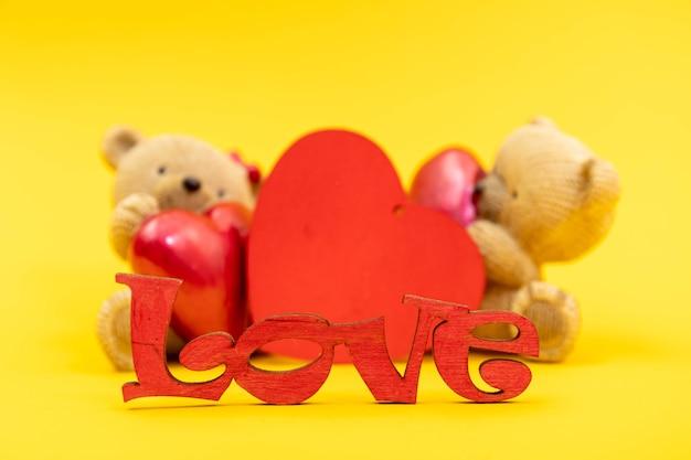 Paar teddybär spielzeug und das wort liebe aus holzbuchstaben, rote herzen. valentinstag konzept. postkartenvorlage.