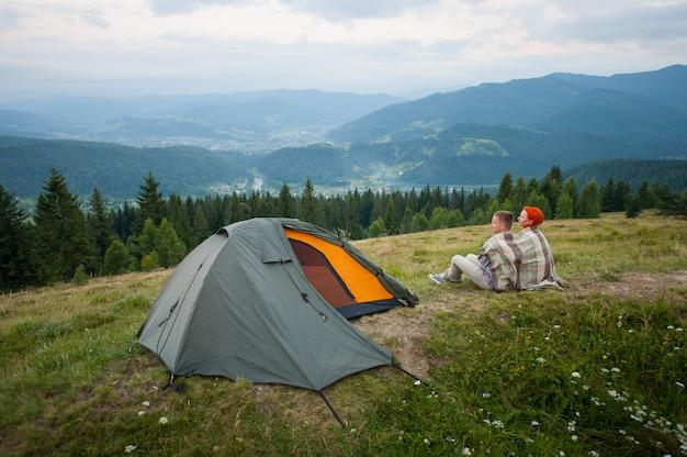 Paar touristen bedeckt mit einem plaid auf einem hügel in der nähe des zeltes sitzen