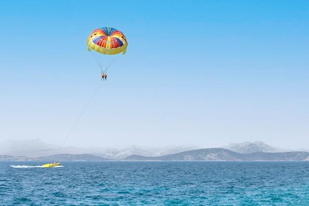 Paar touristen, die auf einem bunten fallschirm auf blauem himmelhintergrund fliegen. kopieren sie platz, urlaub spaß aktivitäten. meer sommer erholung - türkei.