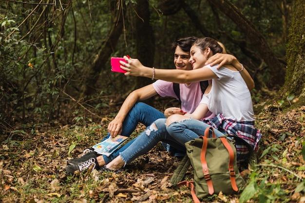 Paar touristen, die selbstporträt mit kamerahandy im dschungel nehmen