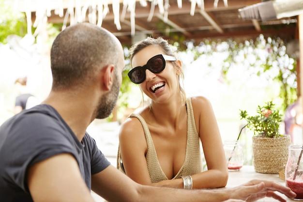 Paar touristen, die sich im restaurant im freien ausruhen. reisende menschen, die während der ferien zum mittagessen zusammen gesundes essen essen.