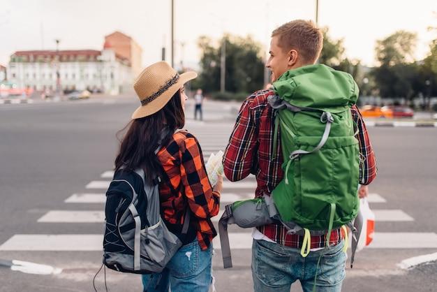 Paar touristen mit rucksäcken, rückansicht, ausflug in die stadt. sommerwandern. wanderabenteuer von jungem mann und frau, stadtwandern