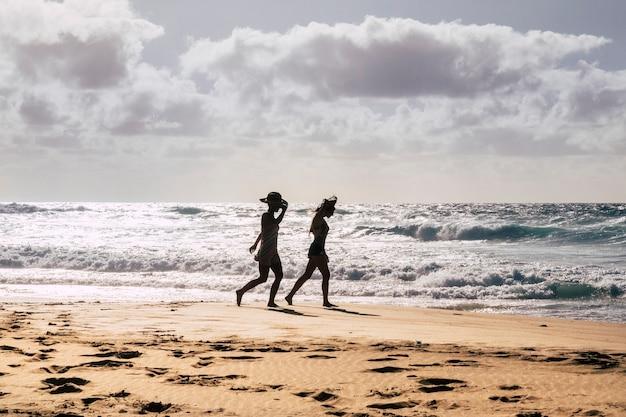 Paar touristische mädchen, die während der sommerferien am ufer am strand spazieren gehen