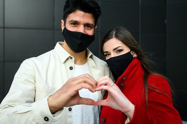 Paar trägt masken und macht das zeichen eines herz-, covid- und coronavirus-konzepts