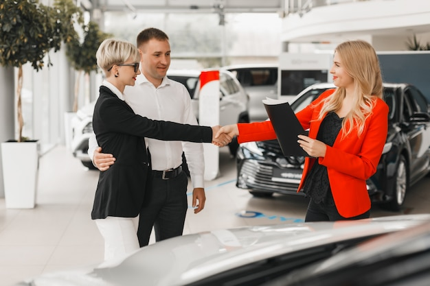 Paar treffen mit autohändler für den kauf des autos.