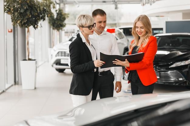 Paar treffen mit dem händler für die auswahl und den kauf des autos.