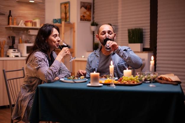Paar trinken rotwein mit beziehungsfeier. glückliches paar reden, am tisch im esszimmer sitzen, das essen genießen, ihr jubiläum zu hause mit romantischer zeit feiern.